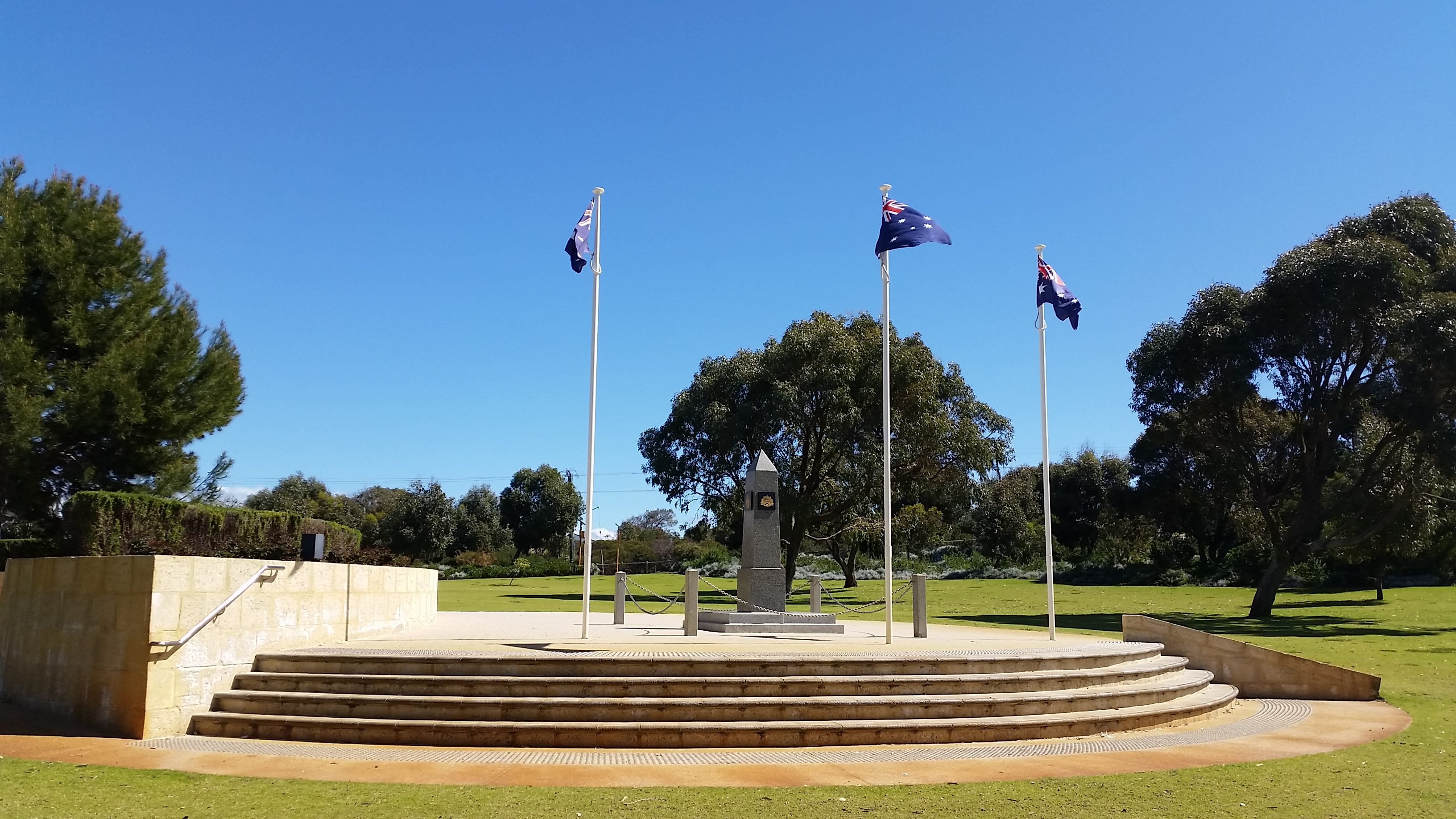 A war memorial located in an open park with large trees in the background and three flagpoles with Australian flags flying.