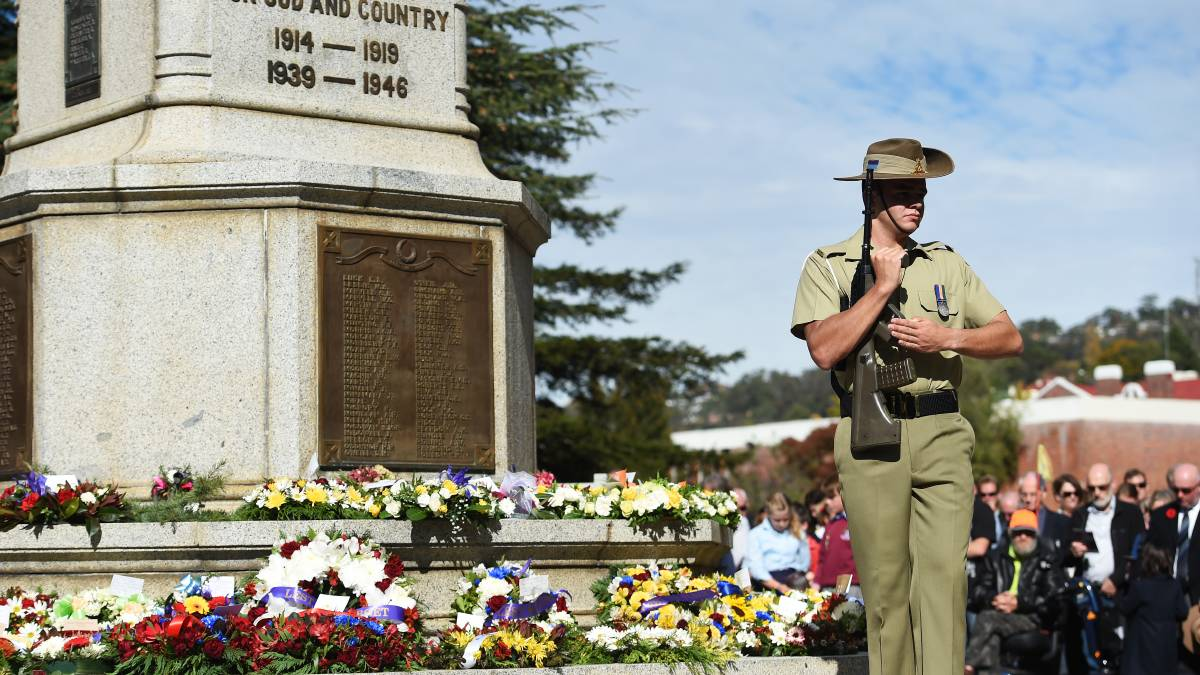 A solider holding a rifle standing in front of a war memorial which has many colourful wreaths at its base. A crowd of people are looking on in the background.