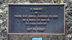 The memorial plaque, dedicated to all who have served, suffered or died