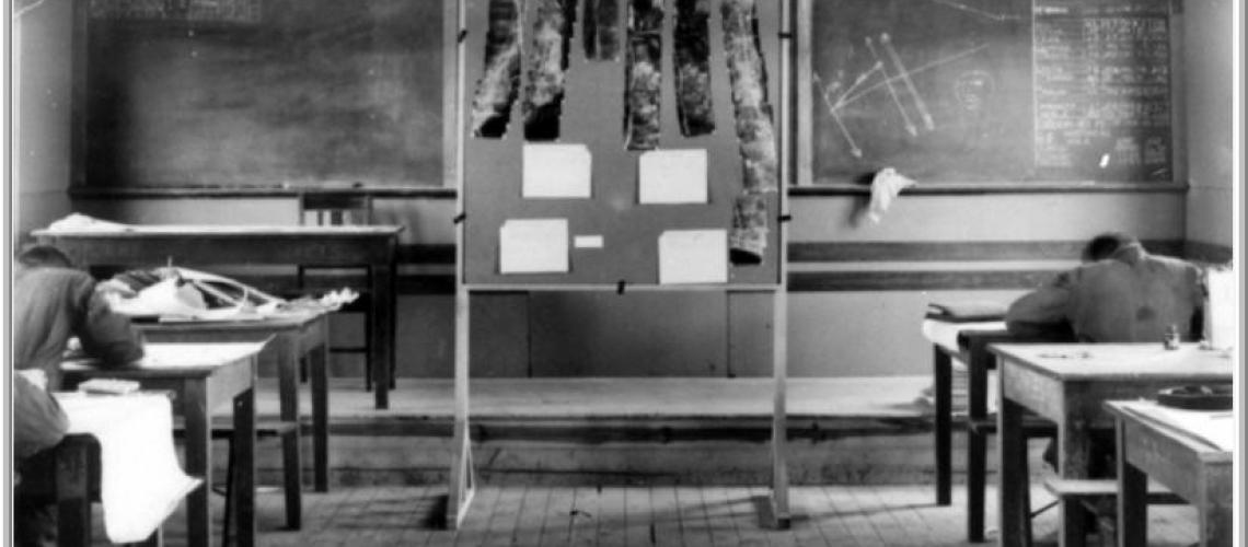Classroom interior revealing trigonometry, charts and aerial photographs.