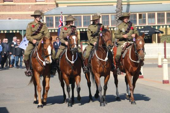 Four horses and their riders in an Anzac Day parade