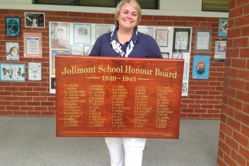 Principal of Jolimont Primary School Barbara Iffla holding Jolimont School Honour Board