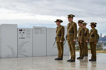 Image of Australian soldier and graphics on perforated memorial panels, and soldiers at the opening, photography by CDI.